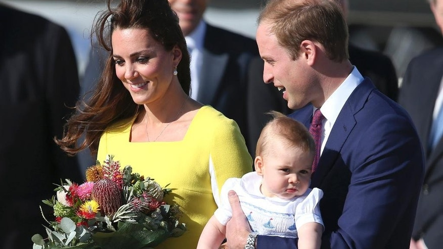 Britain's Prince William holding his son Prince George and his wife Kate, Duchess of Cambridge, arrive in Sydney Wednesday, April 16, 2014. The royal couple are on a three-week tour of Australia and New Zealand, the first official trip overseas with their son, Prince George. (AP Photo/Rob Griffith)