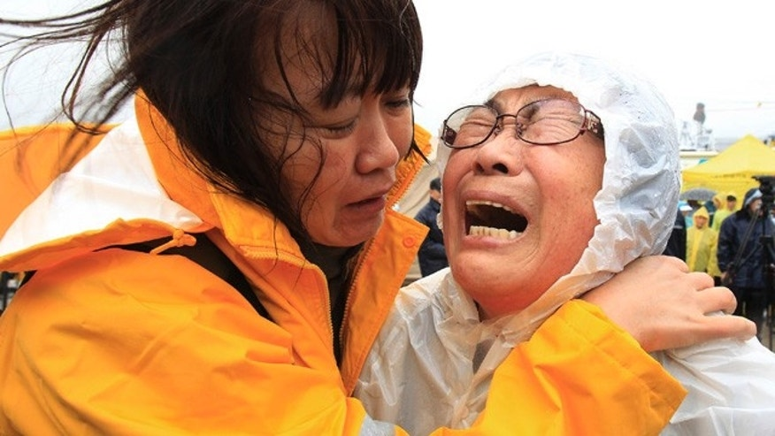April 17, 2014: Relatives of a passenger aboard a sunken ferry weep as they wait for the news on the rescue operation at a port in Jindo, South Korea.  Strong currents, rain and bad visibility hampered an increasingly anxious search Thursday for more than 280 passengers still missing a day after their ferry flipped onto its side and sank in cold waters off the southern coast of South Korea. (AP Photo/Ahn Young-joon)