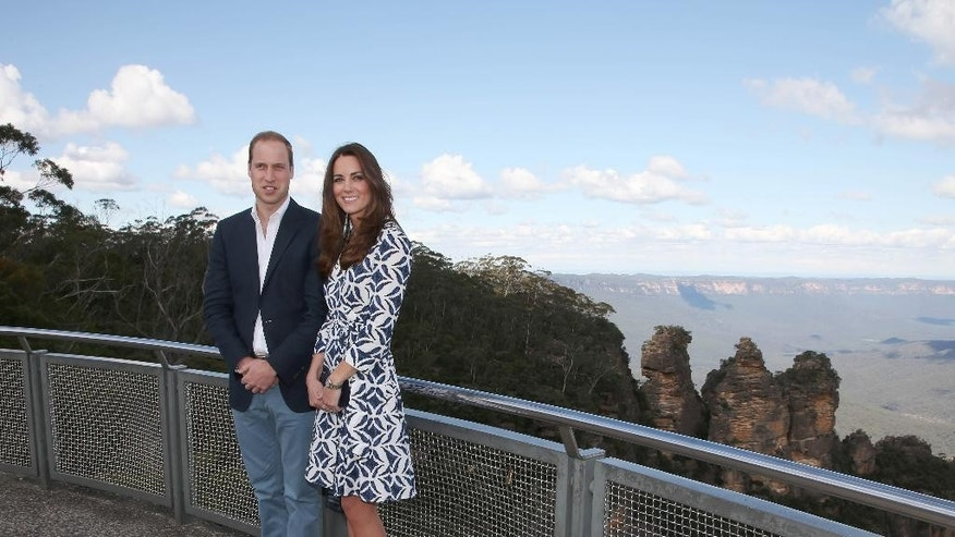 Britain's Prince William and his wife, Kate, the Duchess of Cambridge, pose in front of the Three Sisters rock formation in the Blue Mountains during a tour of Echo Point in Katoomba, Australia Thursday, April 17, 2014. The royal couple, along with Prince George, are on the 10-day official visit. (AP Photo/Rick Rycroft, Pool)