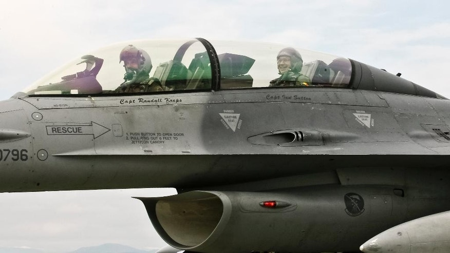 CAPTION CORRECTION, CORRECTS BYLINE - Romanian prime minister Victor Ponta, right, smiles from the cockpit of a US Air Force F-16 fighter jet piloted by Maj. Dustin Yogi Brown during a military exercise in Campia Turzii, Romania, Thursday, April 17, 2014. Dressed in a flight suit, Ponta visited the Campia Turzii military air base in northwest Romania where about 450 U.S. and Romanian troops and technical staff had been taking part in the weeklong exercises ending Thursday. (AP Photo/Mihaela Bobar)