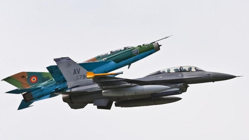 A Russian made MIG 21 fighter jet maneuvers next to a US Air Force F-16 piloted by Maj. Dustin Yogi Brown, right, and transporting Romanian Premier Victor Ponta during a military exercise in Campia Turzii, Romania, Thursday, April 17, 2014. Dressed in a flight suit, Ponta visited the Campia Turzii military air base in northwest Romania where about 450 U.S. and Romanian troops and technical staff had been taking part in the weeklong exercises ending Thursday. (AP Photo/Mircea Rosca)