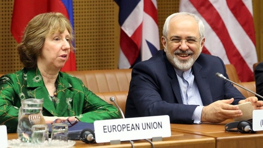 April 8, 2014: European foreign policy chief Catherine Ashton, left, and Iranian Foreign Minister Mohamad Javad Zarif, right, wait for the start of closed-door nuclear talks in Vienna, Austria. (AP Photo/Ronald Zak)