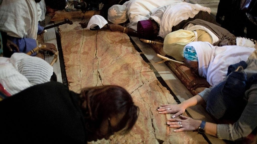 Worshippers pray by the Stone of Unction, where according to Christianity Jesus was laid after he was crucified during the Washing of the Feet ceremony inside the Church of the Holy Sepulcher, traditionally believed by many to be the site of the crucifixion and burial of Jesus Christ, in Jerusalem, Thursday, April 17, 2014. Orthodox Christians from around the world are in the Holy Land marking the solemn period of Easter. (AP Photo/Ariel Schalit)