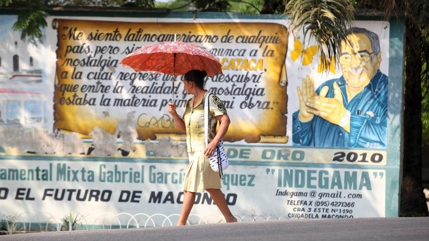 A woman walks past a mural of Nobel laureate Gabriel Garcia Marquez in Aracataca, the city were he was born in Colombia's Caribbean coast, Friday, April 18, 2014. Garcia Marquez died in Mexico City on April 17, 2014. (AP Photo/Ricardo Mazalan)