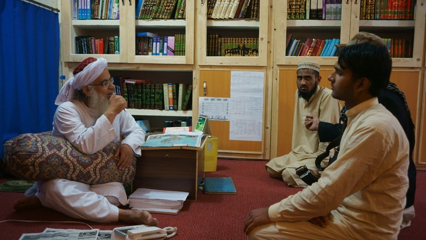 April 18, 2014 - Maulana Abdul Aziz, left, head cleric of a Pakistani seminary, in a library named after slain al Qaeda leader Usama bin Laden in Islamabad, Pakistan.