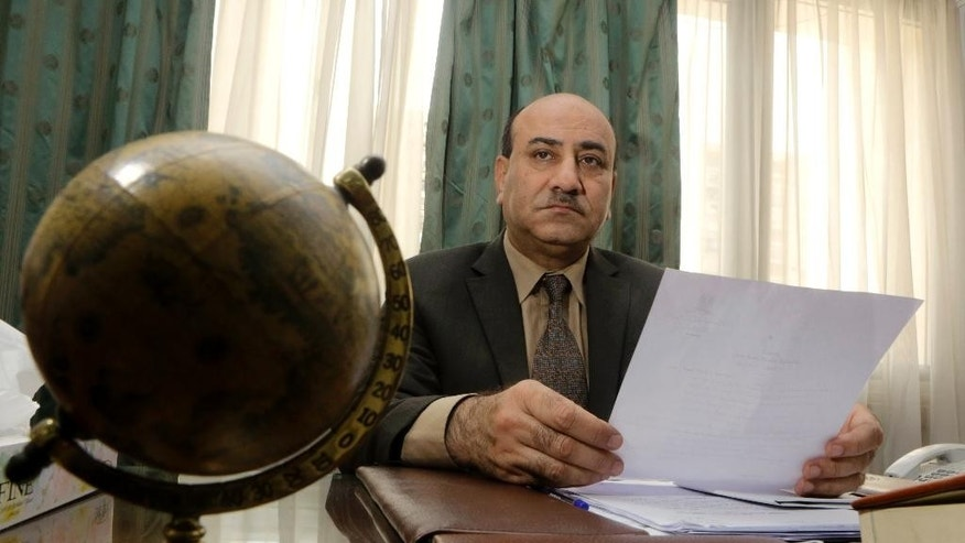 In this Tuesday, April 16, 2014 photo, Hesham Genena, the head of Egypt's oversight body, holds documents at his office in Cairo, Egypt. Genena has created uproar simply because he decided to actually do his job. The head of one of Egypt's foremost government oversight agencies, he says he has uncovered billions of dollars-worth of corruption, including in the country's most untouchable institutions, including the police, intelligence agencies, and the judiciary.(AP Photo/Amr Nabil)
