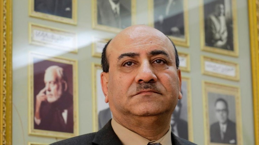 In this Tuesday, April 16, 2014 photo, Hesham Genena, the head of Egypt's oversight body, poses for a portrait in front of pictures of his predecessors at his office in Cairo, Egypt. Genena has created uproar simply because he decided to actually do his job. The head of one of Egypt's foremost government oversight agencies, he says he has uncovered billions of dollars-worth of corruption, including in the country's most untouchable institutions, including the police, intelligence agencies, and the judiciary.(AP Photo/Amr Nabil)