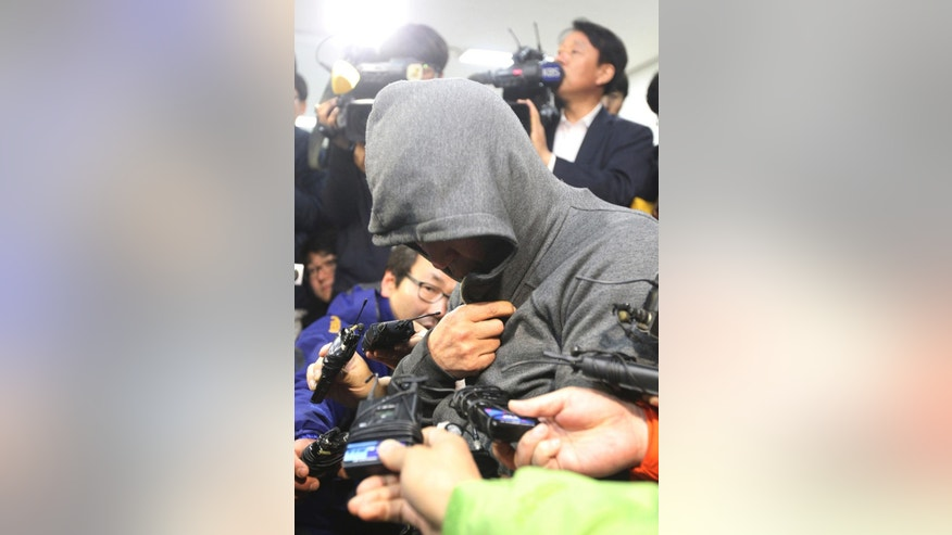 Lee Joon-seok, the captain of a sunken ferry in the water off the southern coast arrives to be investigated at Mokpo Police Station in Mokpo, South Korea, Thursday, April 17, 2014. An immediate evacuation order was not issued for the ferry that sank Wednsday, likely with scores of people trapped inside, because officers on the bridge were trying to stabilize the vessel after it started to list amid confusion and chaos, a crew member said Thursday. (AP Photo/Yonhap)   KOREA OUT