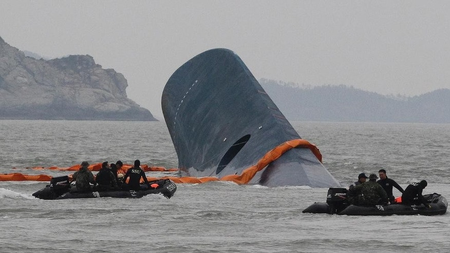 AP10ThingsToSee - South Korean Coast Guard officers search for missing passengers aboard a sunken ferry in the waters off the southern coast near Jindo, South Korea on Thursday, April 17, 2014. An immediate evacuation order was not issued for the ferry, likely with scores of people trapped inside, because officers on the bridge were trying to stabilize the vessel after it started to list amid confusion and chaos, a crew member said Thursday. (AP Photo/Ahn Young-joon)