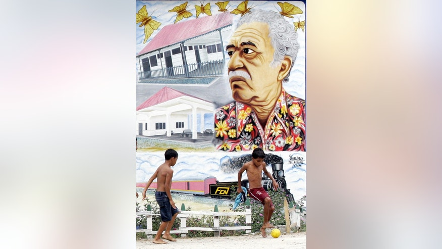 FILE - In this Jan. 4, 2006 file photo, boys play soccer in front a mural of Colombian Nobel laureate Gabriel Garcia Marquez in Aracataca, Colombia, the writer's hometown. Marquez died on Thursday, April 17, 2014 at his home in Mexico City. (AP Photo/Fernando Vergara, File)