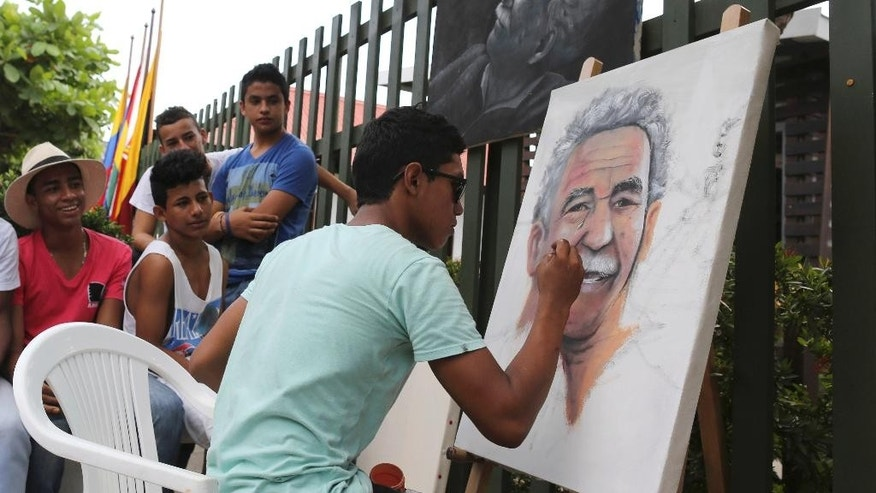 Friends surround Melquin Merchan, an 18-year-old painter from Aracataca, as he paints a portrait of Gabriel Garcia Marquez in front of the house where the Nobel laureate was born in Aracataca, Colombia, Friday, April 18, 2014. Garcia Marquez died at the age of 87 in Mexico City on Thursday. (AP Photo/Ricardo Mazalan)