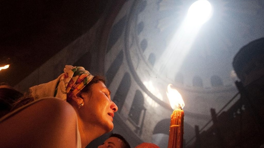 "A Christian pilgrim holds candles at the church of the Holy Sepulcher, traditionally believed to be the burial site of Jesus Christ, during the ceremony of the Holy Fire in Jerusalem's Old City, Saturday, April 19, 2014. The ""holy fire"" was passed among worshippers outside the Church and then taken to the Church of the Nativity in the West Bank town of Bethlehem, where tradition holds Jesus was born, and from there to other Christian communities in Israel and the West Bank. (AP Photo/Dan Balilty)"