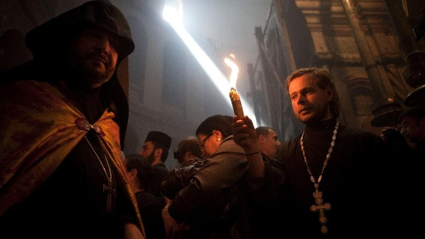 "A Christian priest holds a candle at the church of the Holy Sepulcher, traditionally believed to be the burial site of Jesus Christ, during the ceremony of the Holy Fire in Jerusalem's Old City, Saturday, April 19, 2014. The ""holy fire"" was passed among worshippers outside the Church and then taken to the Church of the Nativity in the West Bank town of Bethlehem, where tradition holds Jesus was born, and from there to other Christian communities in Israel and the West Bank. (AP Photo/Dan Balilty)"