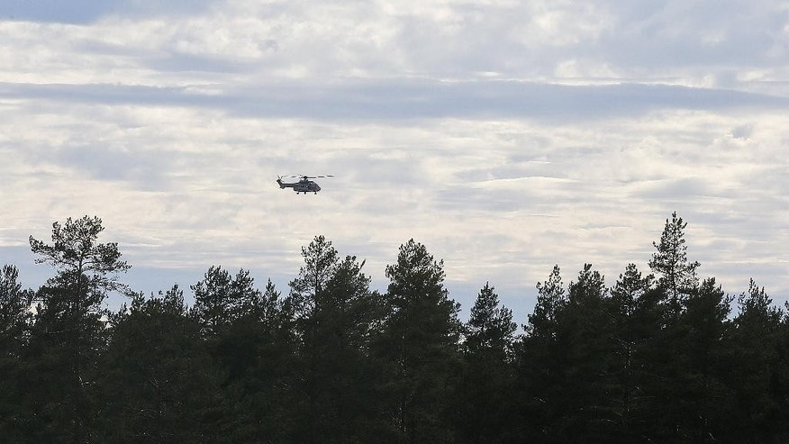 A helicopter flies over the area near the Jamijarvi Airfield, southwest Finland, where a small passenger plane carrying parachuters fell to the ground, Sunday April 20, 2014. At least three people were killed in the crash, three were rescued and five are still missing, local media have reported. (AP Photo/Mika Kenerva, Lehtikuva)     FINLAND OUT