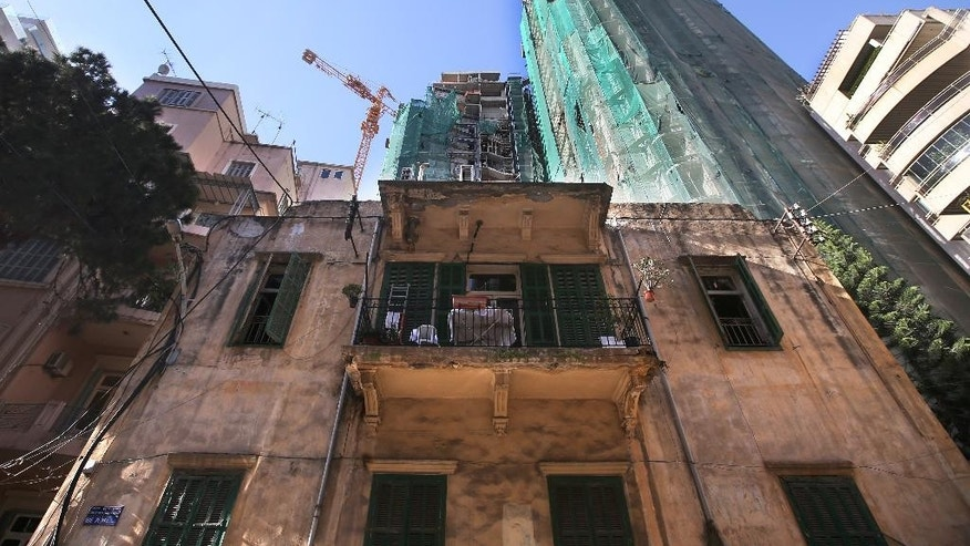 In this April 9, 2014 photo, an old house is overshadowed by newer, taller modern buildings, some still under construction, in Beirut, Lebanon. Beirut is no different than Dubai, Doha or other major world cities overtaken by a global trend for modern, tall buildings. But in a country that prides itself on its rich history, many complain that Lebanon is losing its charm and character, often said to be the only thing going for it. (AP Photo/Hussein Malla)