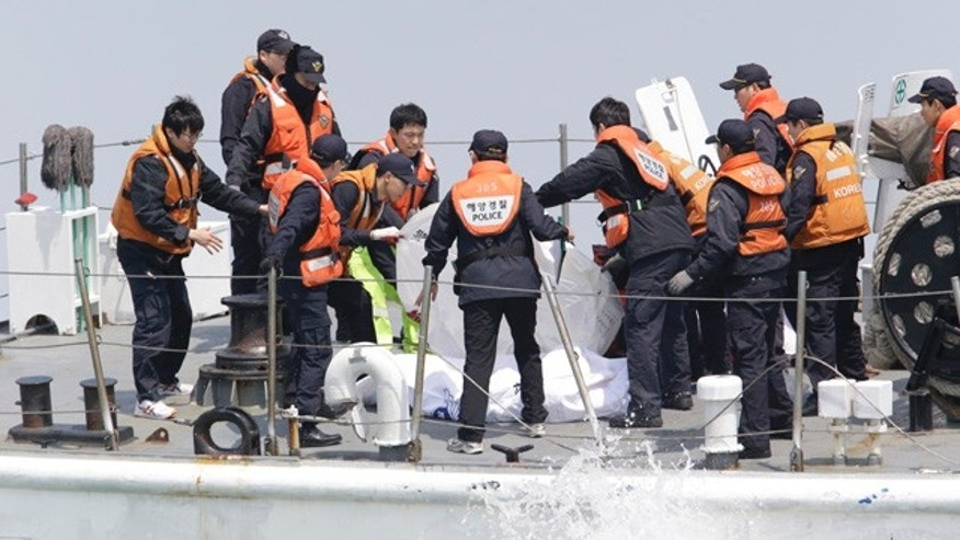 April 20, 2014: South Korean Coast Guard police officers on a boat check the bodies of passengers believed to have been trapped in the sunken ferry Sewol in the water off the southern coast near Jindo, south of Seoul. (AP Photo/Lee Jin-man)