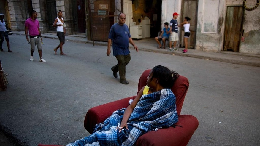 In this March 7, 2014 photo, a woman sitting on a chair waits in a street of Havana, Cuba, to be informed of where she will be relocated after the building where she lived was vacated due to the danger of collapse after the structure failed. Despite reforms in recent years to address the island's housing problem, such building collapses remain common in Cuba, where decades of neglect and a dearth of new apartments has left untold thousands of islanders living in crowded structures at risk of suddenly falling down.  (AP Photo/Ramon Espinosa)