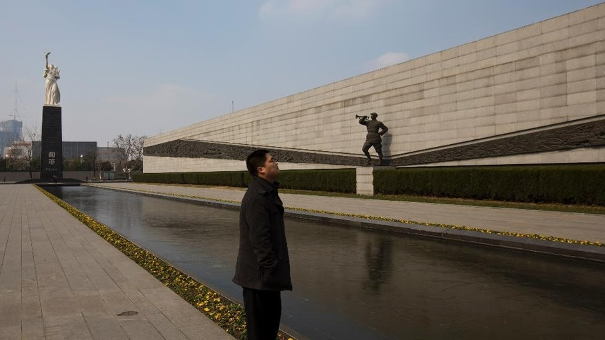 In this Feb. 11, 2014 photo, a visitor stands near sculptures at Nanjing Massacre Memorial Hall in Nanjing, in eastern China's Jiangsu province. The Tokyo shrine and the memorial hall in Nanjing, as Nanking is now called, are physical embodiments of divergent views of history that still strain China-Japan relations, 70 years after the war. They complicate America's objective of maintaining peace and stability in the Pacific, as President Barack Obama starts a 4-country Asian tour in Japan this week. The implications are potentially serious, particularly over contested uninhabited islands called the Senkaku by Japan and Diaoyu by China. (AP Photo/Alexander F. Yuan)