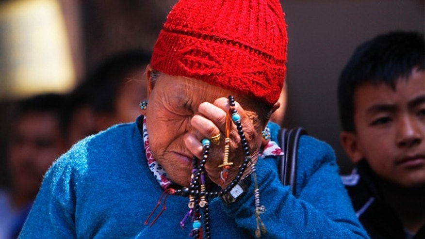 April 19, 2014: The mother of Nepalese mountaineer Ang Kaji Sherpa, killed in an avalanche on Mount Everest, holds prayer beads in her hand and cries while she waits for his body at Sherpa Monastery in Katmandu, Nepal  (AP Photo/Niranjan Shrestha)