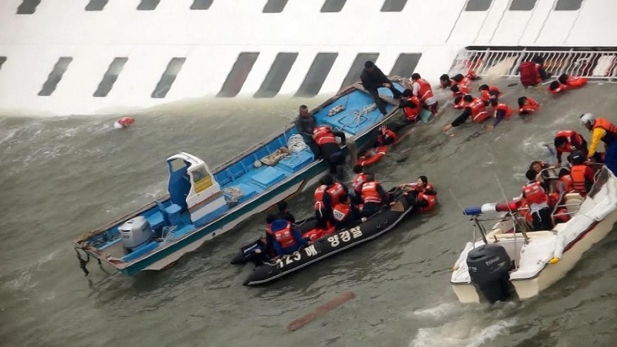 FILE - In this April 16, 2014 file image taken from video from Mokpo Coast Guard, passengers from the Sewol, a South Korean ferry sinking off South Korea's southern coast, are rescued by South Korean Coast Guard personnel in the water off the southern coast near Jindo, south of Seoul. As the ferry sank, some crew members gave their lifejackets to passengers. One refused to leave until she shepherded students off the ship, and was later found dead. Others worked from rescue boats to break windows with hammers and pull people trapped in cabins to safety. (AP Photo/Yonhap, File) KOREA OUT
