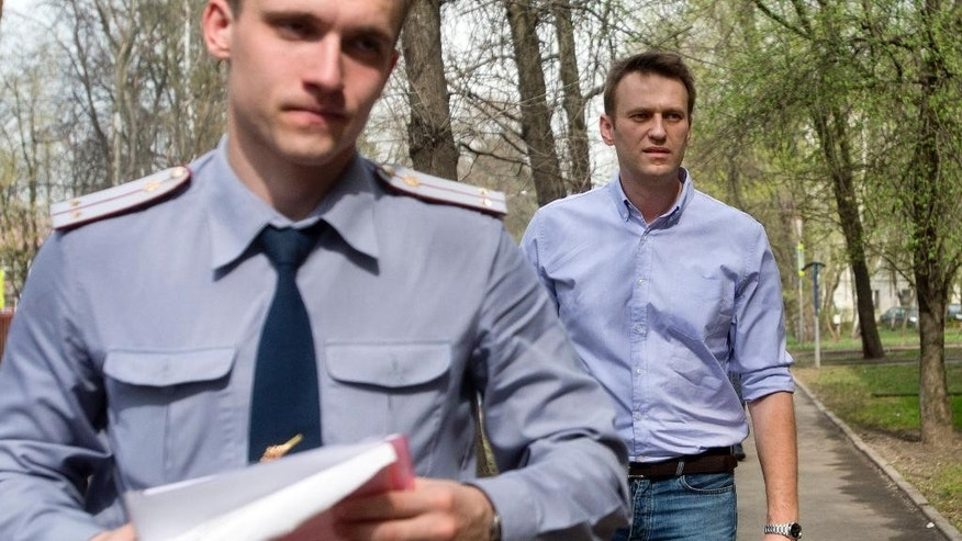 Russian opposition activist and anti-corruption crusader Alexei Navalny, right, is escorted  to a court by a policeman, left, from his  home, where he is currently staying under house arrest in Moscow, Russia, Tuesday, April 22, 2014. Russian opposition leader and anti-corruption crusader Alexei Navalny was found guilty in a libel case and fined US$8,400 in a court ruling that left the door open for his subsequent jailing. (AP Photo/Pavel Golovkin)