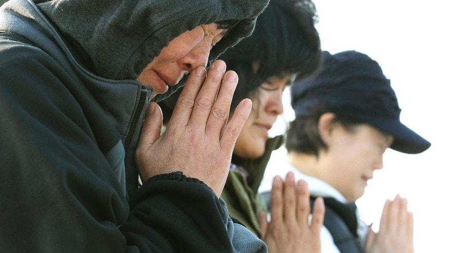 Relatives of passengers aboard the sunken ferry Sewol pray as they wait for their missing loved ones at a port in Jindo, South Korea, Monday, April 21, 2014. Divers continued the grim work of recovering bodies from inside the sunken South Korean ferry Monday, as a newly released transcript showed the ship was crippled by confusion and indecision well after it began listing. The transcript suggests that the chaos may have added to a death toll that could eventually exceed 300. (AP Photo/Ahn Young-joon)