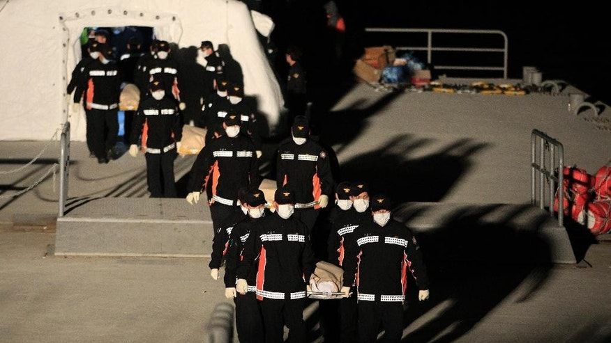 Bodies of a passengers aboard the Sewol ferry which sank in the water off the southern coast, are carried by rescue workers upon their arrival at a port in Jindo, South Korea, Monday, April 21, 2014. Divers continued the work of recovering bodies from inside the sunken ferry Monday, as a newly released transcript showed the ship was crippled by confusion and indecision well after it began listing. The transcript suggests that the chaos may have added to a death toll that could eventually exceed 300. (AP Photo/Ahn Young-joon)