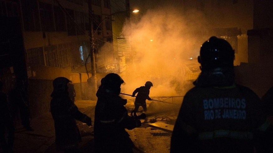 Firefighters put out a burning barricade during clashes at the Pavao Pavaozinho slum in Rio de Janeiro, Brazil, Tuesday, April 22, 2014. Intense exchanges of gunfire, numerous blazes set alit and a shower of homemade explosives and glass bottles onto a busy avenue in Rio de Janeiro's main tourist zone erupted Tuesday night after the death of a popular young shantytown resident. (AP Photo/Felipe Dana)
