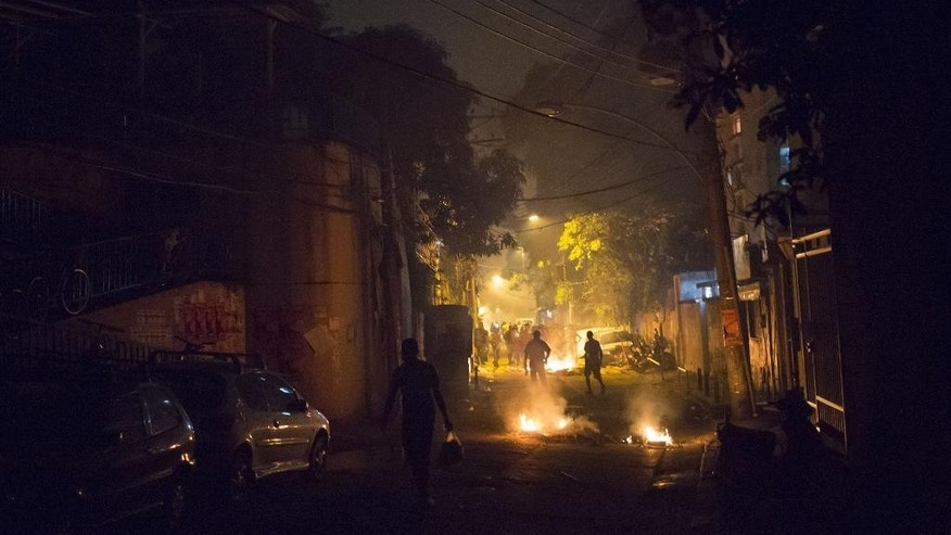 Residents walk among burning barricades during clashes at the Pavao Pavaozinho slum in Rio de Janeiro, Brazil, Tuesday, April 22, 2014. Intense exchanges of gunfire, numerous blazes set alit and a shower of homemade explosives and glass bottles onto a busy avenue in Rio de Janeiro's main tourist zone erupted Tuesday night after the death of a popular young shantytown resident. (AP Photo/Felipe Dana)