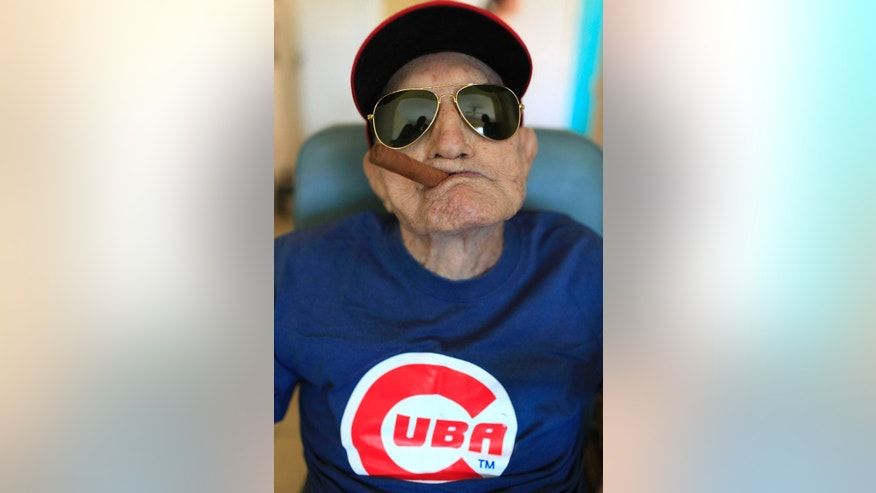 "FILE - In this April 25, 2013 file photo, Conrado Marrero, the world's oldest living former Major League Baseball player, poses for a photo on his 102 birthday at his home in Havana, Cuba. Family members say Marrero has died in Havana. He was 102, just two days short of his 103rd birthday. Grandson Rogelio Marrero confirmed the death on Wednesday, April 23, 2014. Marrero was a diminutive right-hander who went by the nickname ""Connie"" when he pitched for the Washington Senators in the 1950s. (AP Photo/Franklin Reyes, File)"
