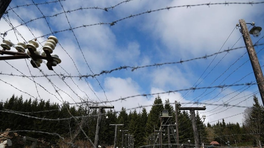 In this picture taken near the village of Kvilda, Czech Republic, on Wednesday, April 9, 2014 the reconstruction of Iron Curtain stands in the Sumava National Park. The Iron Curtain was traced by a real electrified barbed-wire fence that isolated the communist world from the West.  It was an impenetrable Cold War barrier _ and for some inhabitants of the Czech Republic it still is.  Deer still balk at crossing the border with Germany even though the physical fence came down a quarter century ago, with the painful Cold War past apparently still governing their behavior, new studies show.  (AP Photo/Petr David Josek)