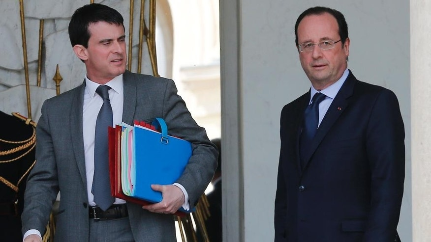 French Prime Minister Manuel Valls, left, and French president Francois Hollande  leave at the end of the Cabinet meeting at the Elysee Palace in Paris Wednesday, April . 23, 2014. (AP Photo/Jacques Brinon)