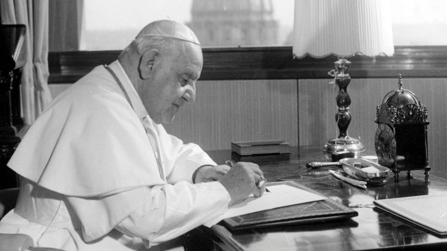 "FILE - In this April 15, 1963 file photo, Pope John XXIII sits at his working desk in his studio in a IX century tower in the Vatican gardens. In background the dome of St. Peter's Basilica. The Pontiff found the tower - once a fortress and later the Vatican observatory - abandoned and in decay. He liked it, particularly for the beautiful view from its covered terrace, embracing a great part of Rome and the surrounding country, in clear weather as far as the sea, distant about 25 kilometers (16 miles). He had it repaired and spends many days working in the studio he has had arranged there. While much of the focus of Sunday's dual canonization will be on Pope John Paul II's globe-trotting, 26-year papacy and his near-record sprint to sainthood, many older Catholics will be celebrating the short but historic pontificate of the ""Good Pope,"" John XXIII. (AP Photo/Luigi Felici, File)"