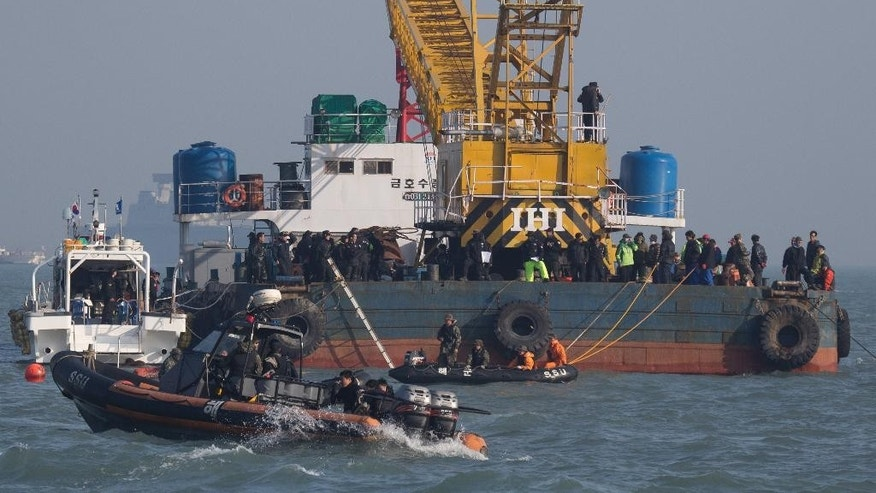 In this Tuesday, April 22, 2014, searchers and divers look for people believed to have been trapped in the sunken ferry Sewol in the water off the southern coast near Jindo, south of Seoul, South Korea. One by one, coast guard officers carried the newly arrived bodies covered in white sheets from a boat to a tent on the dock of this island, the first step in identifying a sharply rising number of corpses from the South Korean ferry that sank nearly a week ago. (AP Photo/Korea Pool)  KOREA OUT