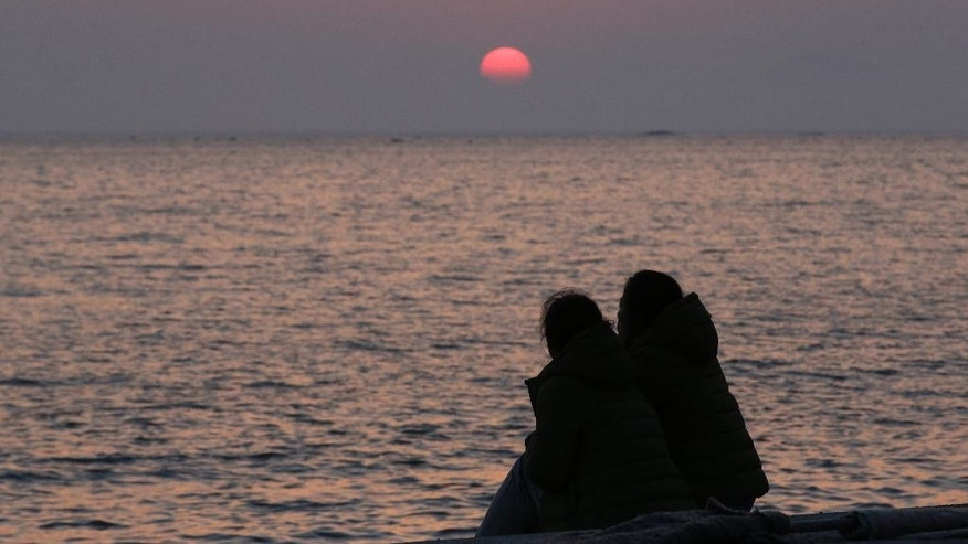 Relatives of passengers aboard the sunken ferry Sewol look towards the sea as they await news on their missing loved ones at sunset at a port in Jindo, south of Seoul, South Korea, Tuesday, April 22, 2014. One by one, coast guard officers carried the newly arrived bodies covered in white sheets from a boat to a tent on the dock of this island, the first step in identifying a sharply rising number of corpses from a South Korean ferry that sank nearly a week ago. (AP Photo/Lee Jin-man)