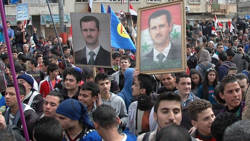 Feb. 11, 2014: In this file photo released by the Syrian official news agency SANA, supporters of Syrian President Bashar Assad, hold up his portraits as they march during a demonstration is solidarity with government forces, in the al-Inshaat neighborhood of Homs, Syria.