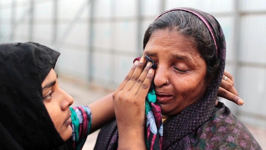 A Bangladeshi girl wipes tears from the eyes of a woman who lost a relative in the Rana Plaza building collapse, at the site of the accident, the worst in the history of the garment industry, on the eve of the tragedy in Savar, near Dhaka, Bangladesh, Wednesday, April 23, 2014. More than 1,100 people were killed when the illegally constructed, 8-storey building collapsed on April 24, 2013, in a heap along with thousands of workers in the five garment factories in the building. (AP Photo/A.M. Ahad)