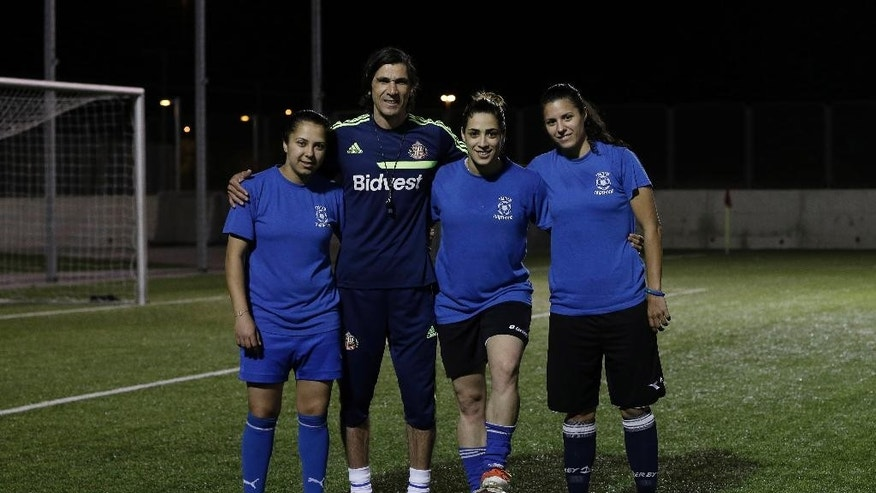 In this Tuesday, April 22, 2014 photo, from left to right, Israeli Arab players Hanin Gamal Nasser, Walaa Hussien and Noura Abu-Shanab pose with their coach during a practice session in Petah Tikva, Israel. When the Israeli women's soccer team Hapoel Petah Tikva lost a number of its players to Israel's national team ahead of World Cup qualifiers, founder Rafi Subra made a decision that sets the team apart from many of its rivals _ he recruited from the Arab villages of northern Israel. For Hapoel Petah Tikva, the addition of five Arab-Israeli women has made waves in the league, as Arab-Israelis often face discrimination in Israel on and off the field. (AP Photo/Tsafrir Abayov)