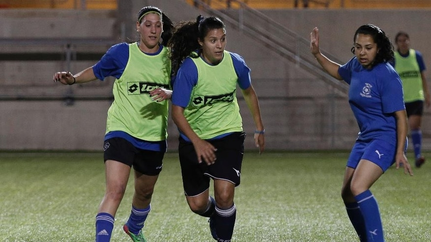 In this Tuesday, April 22, 2014 photo, Israeli Arab Noura Abu-Shanab, center, of Hapoel Petah Tikva soccer team controls the ball during a practice session in Petah Tikva, Israel. When the Israeli women's soccer team Hapoel Petah Tikva lost a number of its players to Israel's national team ahead of World Cup qualifiers, founder Rafi Subra made a decision that sets the team apart from many of its rivals _ he recruited from the Arab villages of northern Israel. For Hapoel Petah Tikva, the addition of five Arab-Israeli women has made waves in the league, as Arab-Israelis often face discrimination in Israel on and off the field. (AP Photo/Tsafrir Abayov)