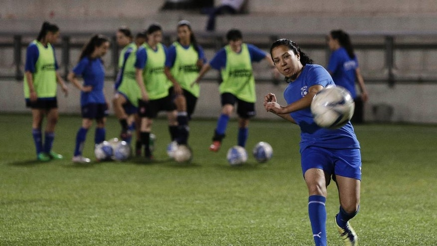 In this Tuesday, April 22, 2014 photo, Israeli Arab player of Hapoel Petah Tikva,  Hanin Gamal Nasser, kicks the ball during a practice session  in Petah Tikva, Tuesday, April 22, 2014. When the Israeli women's soccer team Hapoel Petah Tikva lost a number of its players to Israel's national team ahead of World Cup qualifiers, founder Rafi Subra made a decision that sets the team apart from many of its rivals _ he recruited from the Arab villages of northern Israel. For Hapoel Petah Tikva, the addition of five Arab-Israeli women has made waves in the league, as Arab-Israelis often face discrimination in Israel on and off the field. (AP Photo/Tsafrir Abayov)