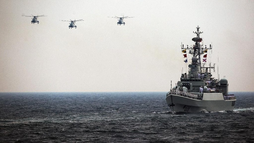 In this April 23, 2009 photo, Chinese Navy helicopters and 528 warship attend an international fleet review to celebrate the 60th anniversary of the founding of the People's Liberation Army Navy in the water off Qingdao of Shandong Province, China. China's boosted defense spending this year grew 12.2 percent to $132 billion, continuing more than two decades of nearly unbroken double-digit percentage increases that have afforded Beijing the means to potentially alter the balance of power in the Asia-Pacific. Outside observers put China's actual defense spending significantly higher, although estimates vary widely.  (AP Photo/Guang Niu, Pool)