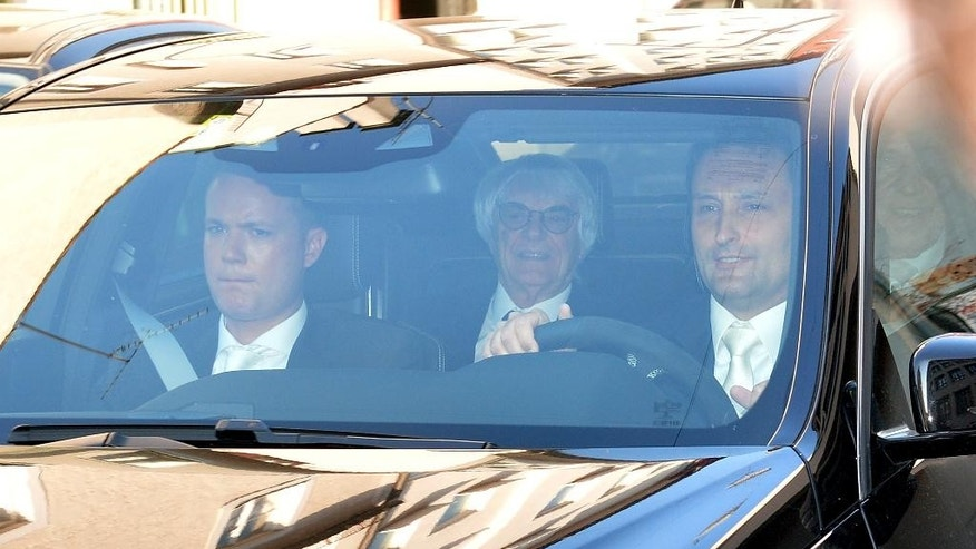 "Bernie Ecclestone, center, the 83-year-old controlling business magnate in Formula One racing, sits in a car on his way to the regional court in Munich , Germany, Thursday, April 24, 2014. Ecclestone is charged with bribery and incitement to breach of trust ""in an especially grave case"" over a US$ 44 million payment to a German banker, that prosecutors allege was meant to facilitate the sale of the Formula One Group to a buyer of Ecclestone's liking. (AP Photo/ Kerstin Joensson)"
