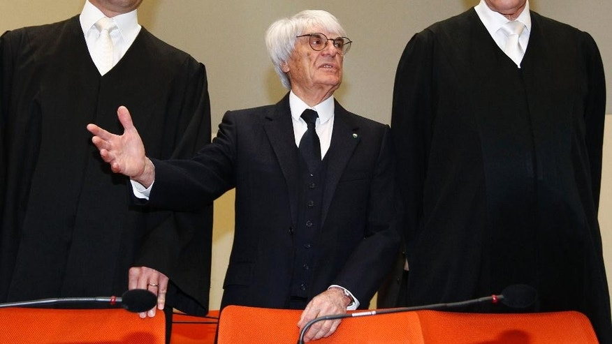 "F1 CEO Bernie Ecclestone, center, stands with his lawyers as he arrives in the  court in Munich, southern Germany, Thursday, April 24, 2014. Ecclestone is charged with bribery and incitement to breach of trust ""in an especially grave case"" over a US$ 44 million payment to a German banker, that prosecutors allege was meant to facilitate the sale of the Formula One Group to a buyer of Ecclestone's liking. (AP Photo/Michaela Rehle, pool)"