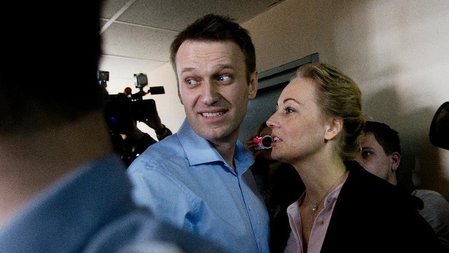 Russian opposition activist and anti-corruption crusader Alexei Navalny, centre, and his wife Yulia, right, enter a courtroom before the start of a trial against Alexei and his brother Oleg Navalny, in Moscow, Russia, Thursday, April 24, 2014.  The brothers face charges of allegedly laundering some millions of rubles from French cosmetics company Yves Rocher. (AP Photo/Pavel Golovkin)