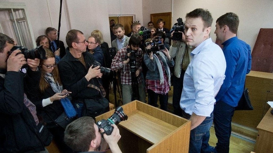 Russian opposition activist and anti-corruption crusader Alexei Navalny, second from right, and his brother Oleg, right, stand in a court room in Moscow before the start of a trial against them on Thursday, April 24, 2014. Alexei Navalny and his brother Oleg face charges of allegedly laundering some millions of rubles from French cosmetics company Yves Rocher.  ( AP Photo/ Pavel Golovkin)