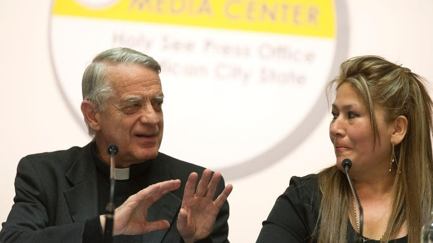 Floribeth Mora, a  Costa Rican woman whose inoperable brain aneurysm purportedly disappeared after she prayed to John Paul II, is flanked by father Federico Lombardi as she attends a press conference at the Vatican, Thursday, April 24, 2014. John Paul II will be made saint together with late Pope John XXIII during a solemn ceremony at the Vatican Sunday.  (AP Photo/Alessandra Tarantino)