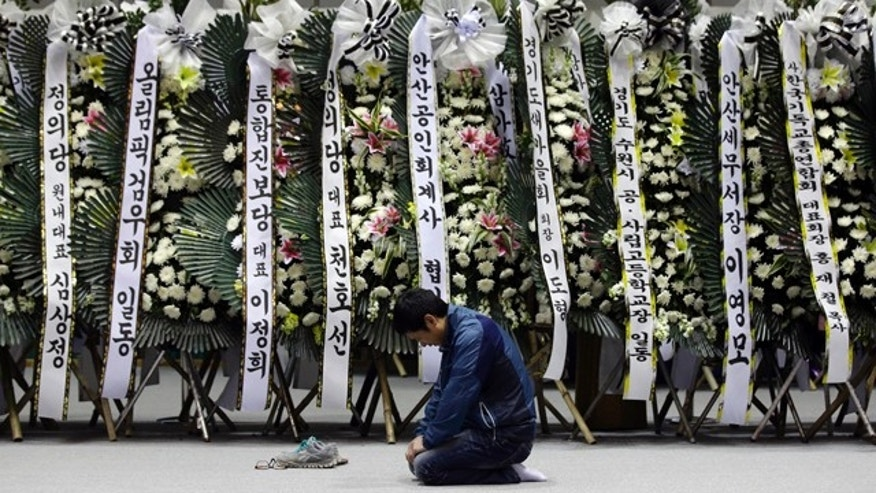 April 24, 2014: A mourner pays tribute to the victims of the sunken ferry Sewol near condolence flowers during a temporary memorial at the auditorium of the Olympic Memorial Museum in Ansan, south of Seoul, South Korea. (AP Photo/Lee Jin-man)