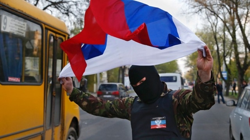 April 22, 2014: A masked pro Russia protestor waves the Russian flag in Donetsk, eastern Ukraine. (AP Photo/Sergei Grits)