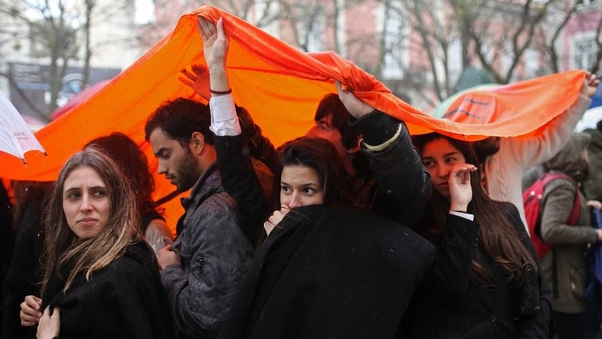In this picture shot April 2 2014, students protect themselves from the rain while protesting cuts in education in Lisbon. For most Portuguese under 50 years old, the revolution is a milestone they learned about at school. But with youth unemployment at 35 percent, the anniversary has struck a chord with many young people. Nationwide commemorations include dozens of protest events organized on social media. (AP Photo/Francisco Seco)
