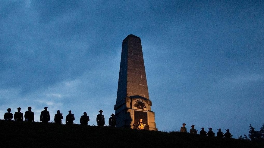 Australian, New Zealand and Belgian soldiers stand on a ridge in front of a World War I monument during an Anzac Day service at Polygon Wood in Zonnebeke, Belgium on Friday, April 25, 2014. Anzac Day is commemorated by New Zealand and Australia to remember the service of those who fought in all wars. (AP Photo/Virginia Mayo)